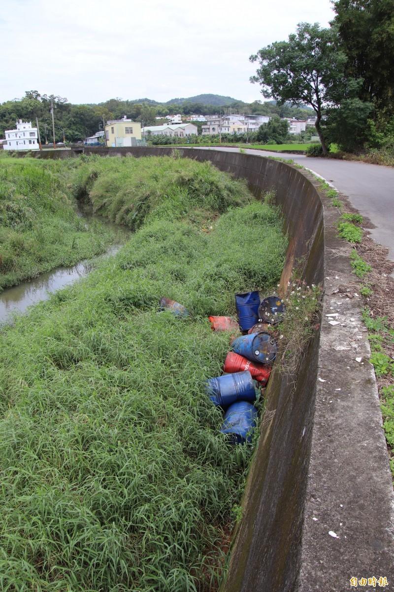 新竹縣新埔鎮大平窩溪行水區內昨天清晨被發現遭人偷丟14桶50加崙裝的廢油桶,新竹檢警獲報不到1個小時就破案,約24小時內完成移除。(記者黃美珠攝)