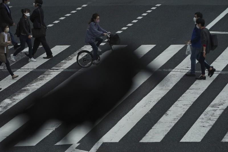 22日東京一處路口,一隻烏鴉停在天橋上,下方戴著口罩的行人走在街頭。(美聯社)