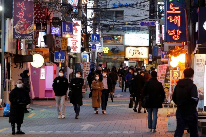 南韓新增確診數日漸緩和,另一方面卻陸續出現「復陽」病例。圖為22日南韓首爾街道,行人均戴上口罩。(路透)