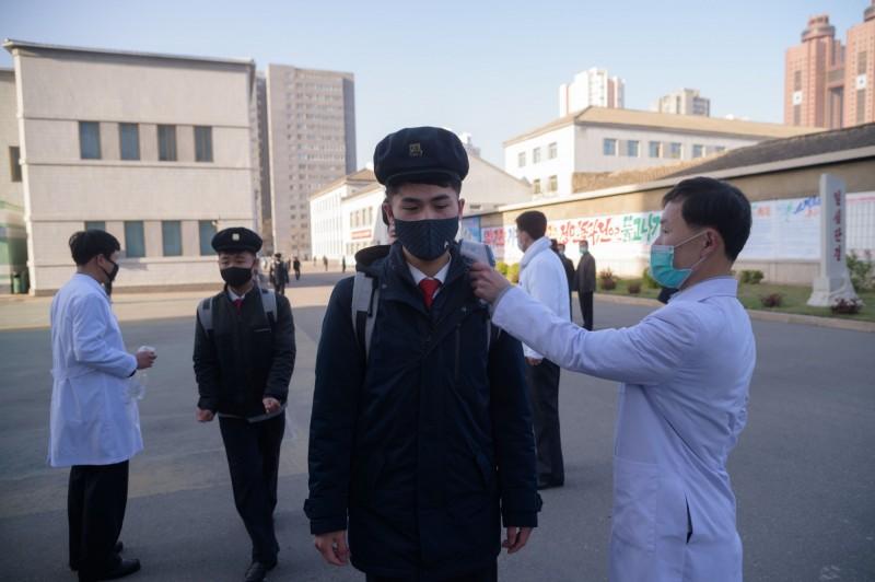 北韓中學生接受體溫檢測。(法新社)