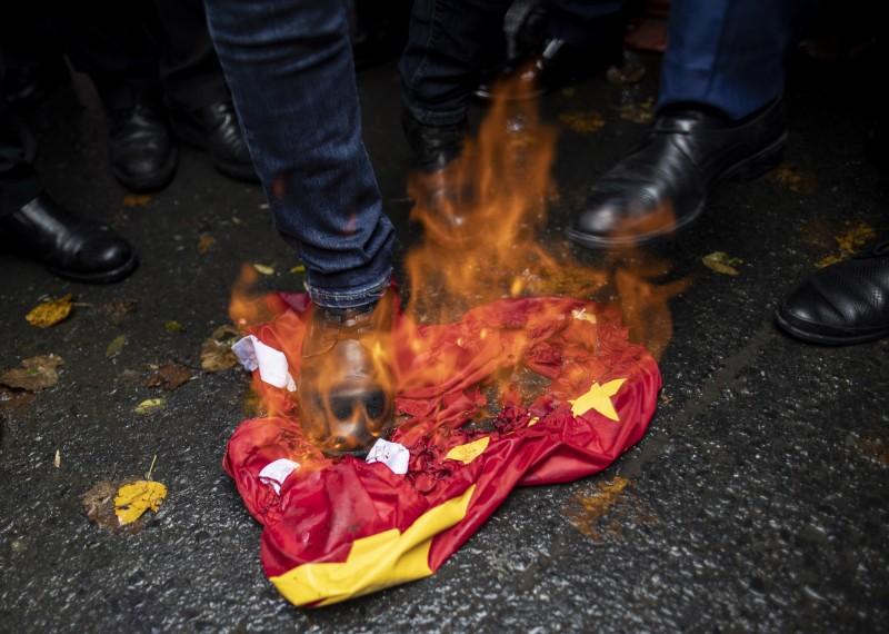 香港首宗因「汙辱國旗罪」而遭起訴的21歲港籍男子,原本法院認為男子態度良好,便輕判他服200小時社會服務;不料香港政府律政司認為刑責過輕申請司法覆核,最後改判男子20天有期徒刑。示意圖,為國外抗議者。(歐新社)