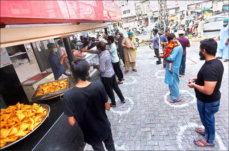 巴基斯坦第二大城拉合爾(Lahore)民眾二十五日保持社交距離,在麵包店前等待購買齋戒月麵包。(美聯社)