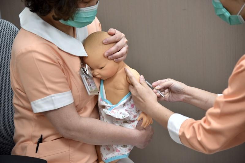 圖為馬偕醫院護理師示範施打卡介苗時家長固定新生兒姿勢。(資料照,馬偕醫院提供)