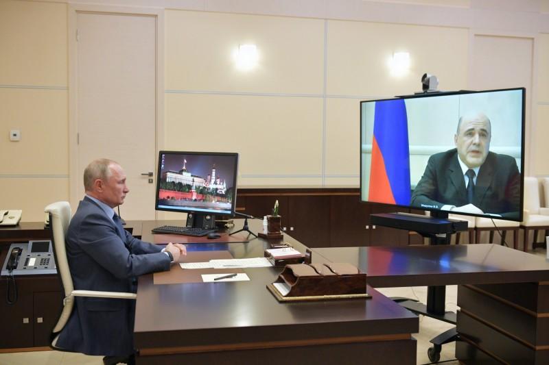 俄羅斯總理米舒斯京(右)向總統普廷(左)報告確診消息。(美聯社)