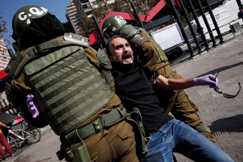 參與示威的智利勞工遭警方強行架走。(歐新社)
