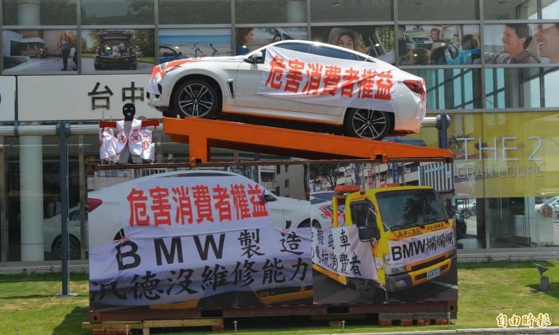 羅姓老闆購買730萬BMWX6M轎車,因交車3個月就出問題,維修後問題沒解決,近日再度把綁上抗議紅布條的轎車,吊到台中烏日的車廠前抗議。 (記者陳建志攝)