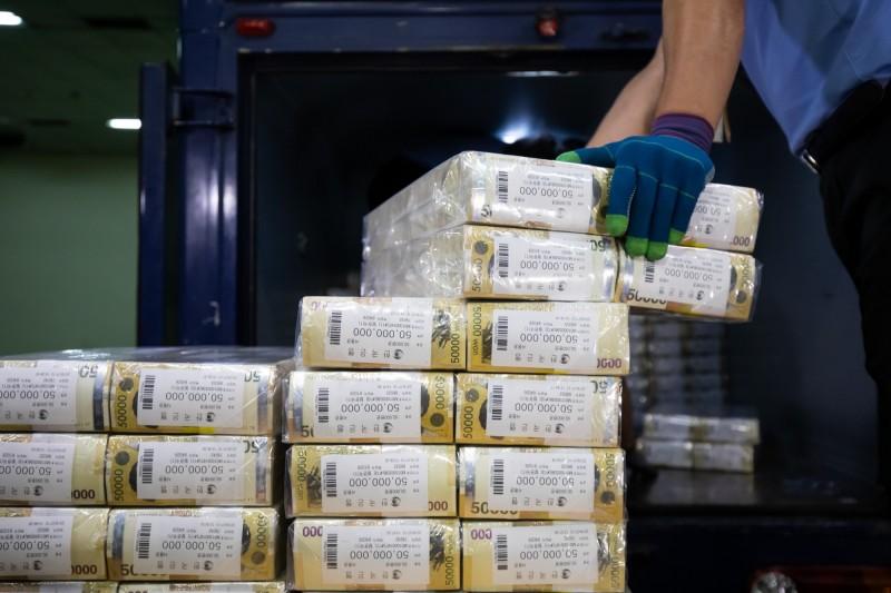 韓國政府今(4日)開始向280萬個弱勢家庭發放武漢肺炎紓困現金,依人數不同每個家庭最高可拿到100萬韓元(約新台幣2.5萬元)。圖為成綑的5萬韓元紙鈔。(彭博)
