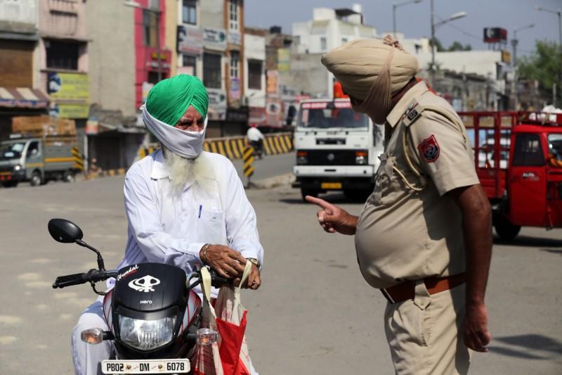 因應疫情,印度近日實行全球封鎖令,日前一名男子因為沒有配戴口罩被警方攔查開單,男子竟搬出父親的名號威脅警方,影片被一旁民眾PO上網,迅速引發外界關注。圖為印度警方詢問民眾通勤目的。(歐新社)