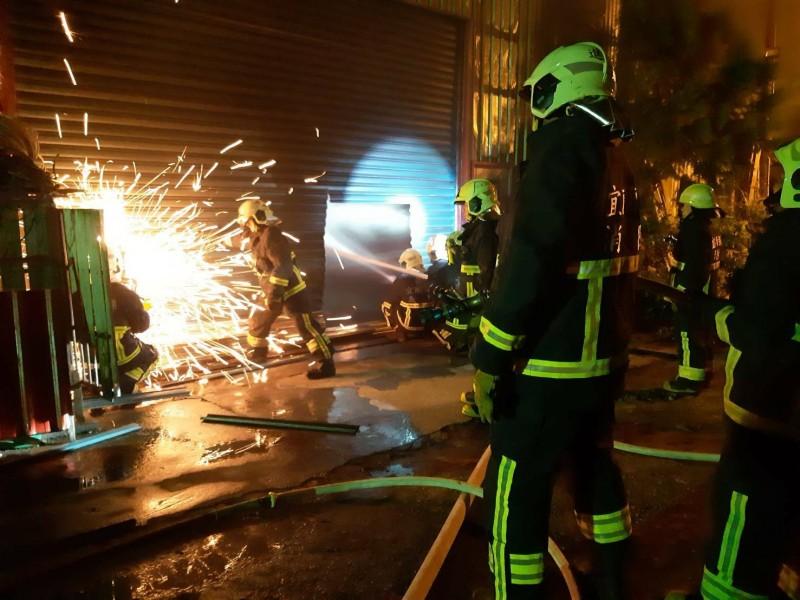 消防人員鋸開鐵皮屋射水滅火。(記者江志雄翻攝)