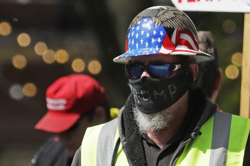 5月1日一名男子戴著寫有「川普」的口罩,抗議華盛頓州居家禁足令防疫措施。(美聯社)
