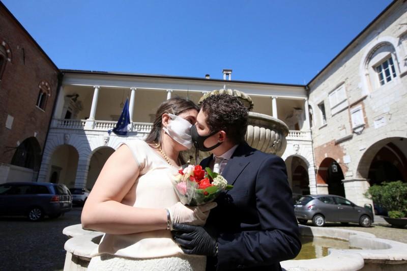 義大利5月18日在全國範圍內將恢復民眾集會和宗教儀式(例如婚禮)。圖為義大利部分已鬆綁地區的新郎新娘舉行結婚儀式,但只能戴著口罩接吻。(歐新社)
