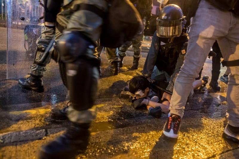 去年8月25日晚間,香港荃灣區爆發警民衝突,圖為一名示威者遭港警壓在地面。(彭博)