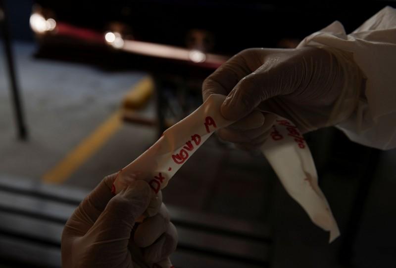 圖為提華納的葬儀人員從屍袋中取下、寫有「武漢肺炎」的標籤。(路透)