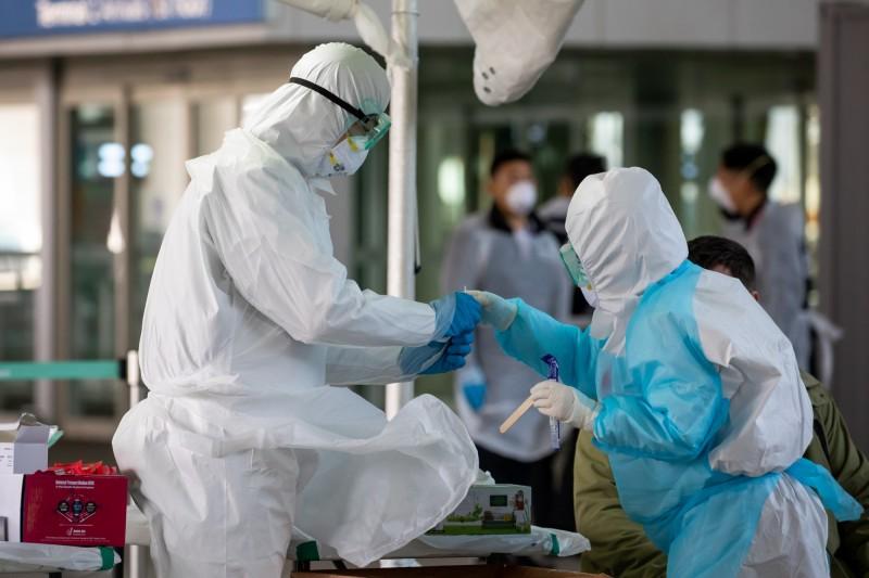 京畿道龍仁市1名29歲男子在確診前連夜狂逛5間夜店,導致南韓本土病例激增,今(9日)新增的18名確診患者當中,就有17人是境內感染。韓國檢疫人員示意圖。(彭博)