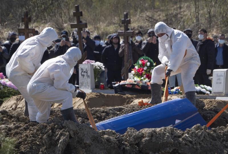 俄羅斯疫情嚴峻,聖彼得堡的殯葬業者身穿防護衣,將染疫身亡者的遺體下葬,並指示親屬保持安全距離觀禮。(美聯社資料照)
