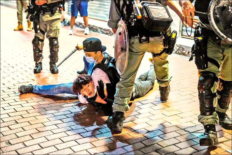 香港「反送中」運動回溫,十日母親節示威者在全港遍地開花;入夜在九龍旺角與警方爆發衝突。上圖為便衣警察壓制一名參與活動的年輕人。(法新社)