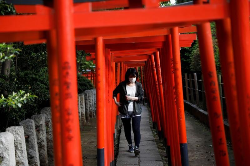 日本政府表示,14日將召開專家會議,研擬是否提早解除39個縣的緊急狀態。圖為配戴口罩的日本民眾走過鳥居。(路透)