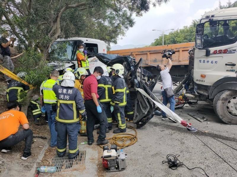 小客車被夾在2輛砂石車之間,車體嚴重變形,車內2人受困,消防人員動用破壞器材搶救中。(讀者提供)