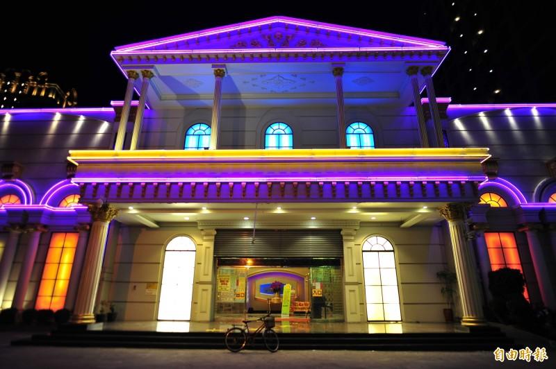 萬象舞廳今天晚上鐵門半拉點亮霓虹燈,為16日開幕做準備。(記者王捷攝)