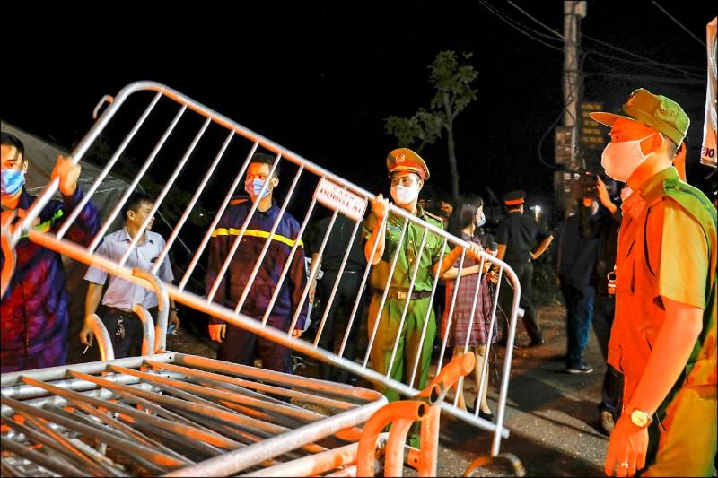 圖為越南警方移除隔離用的路障,民眾則歡欣慶祝。(路透)