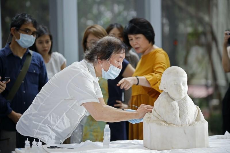 台灣雕刻家黃土水的大理石胸像作品「少女」,經過日籍文物修復師森純一(前左)修復後,10月將在「不朽的青春:台灣美術再發現」特展中,呈現於世人眼前。(中央社,北師美術館提供)
