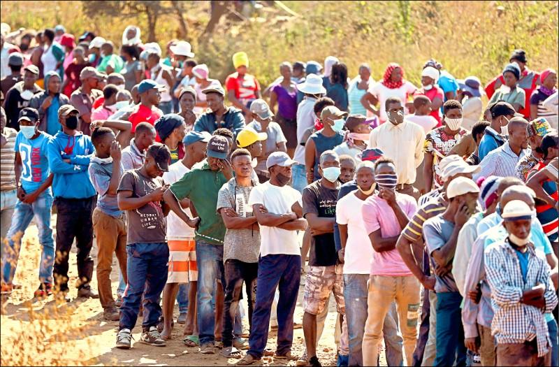 南非首都普勒托利亞附近的工業小鎮桑德蘭里奇的貧困居民,十四日排隊領取發放的食物。惟許多人並未戴口罩和保持社交距離。(路透)