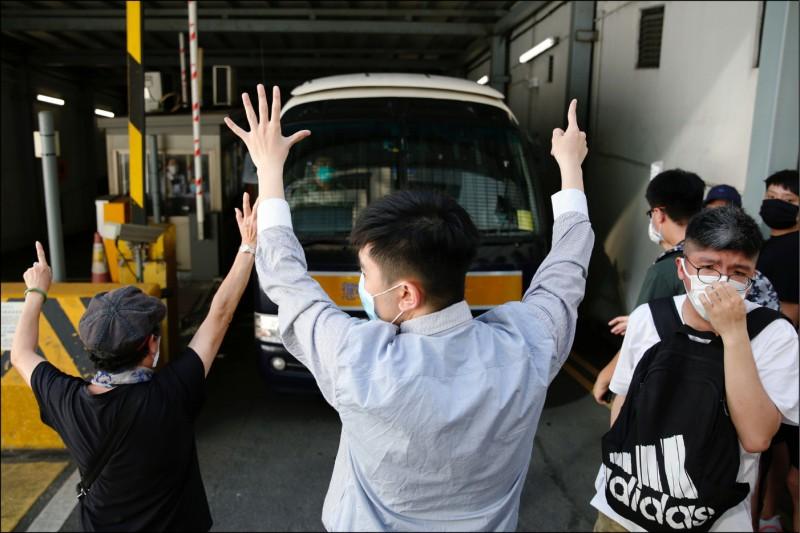 去年6月12日包圍立法會阻止「送中」〈逃犯條例〉二讀的香港救生員冼嘉豪,5月4日成為當庭認暴動罪的「反送中」示威首例。法院15日判他入獄4年,聲援者前往送行,對移送他的囚車高舉「五大訴求,缺一不可」手勢。(路透)
