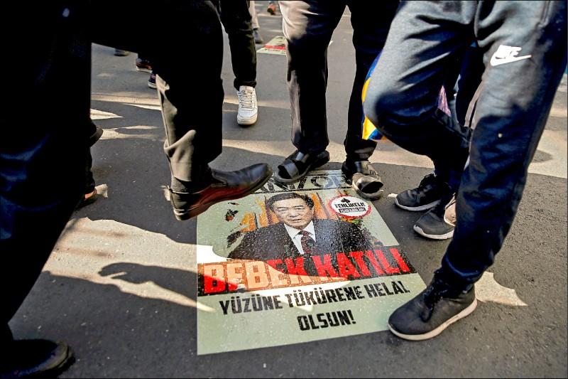 圖為土耳其伊斯坦堡中國領事館前,抗議人士踩踏新疆黨委書記陳全國海報。(路透檔案照)