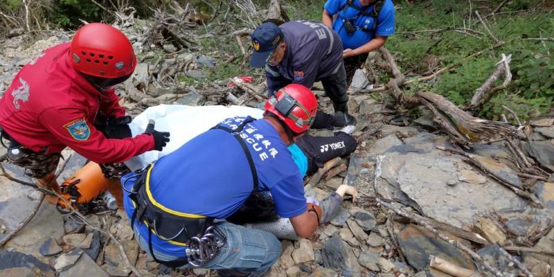 神鷹搜救隊和仁愛消防搜救人員將搶救無效女大生蓋上白布,準備將遺體吊上登山步道。(南投消防局提供)