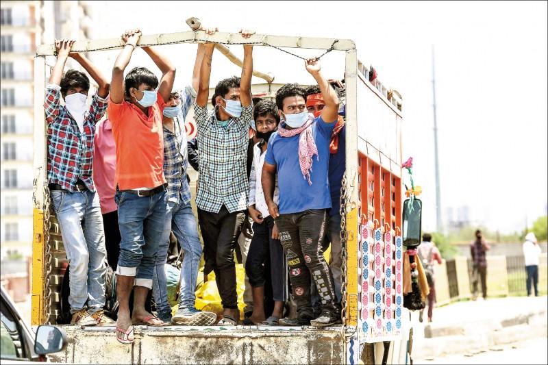 印度政府放寬旨在抗疫的「封城」措施後,幾名出外打拚的移工及其家人十六日搭卡車,穿越德里與「北方省」的交界返鄉。(法新社)