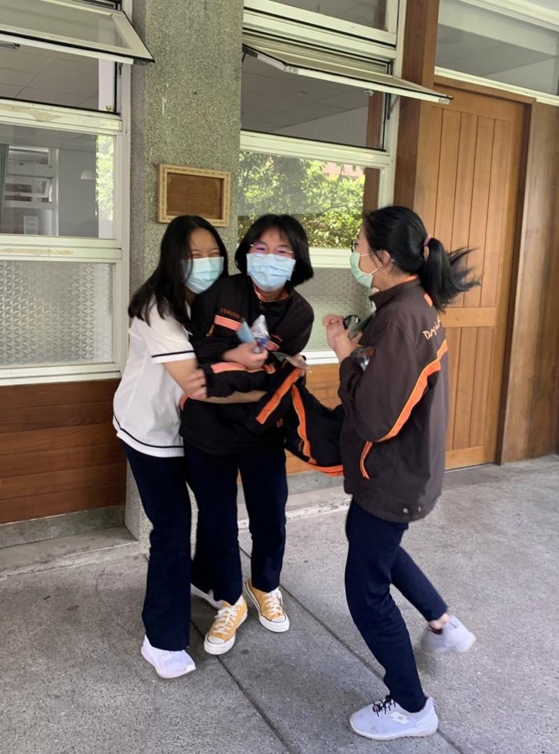 國中會考結束考生走出試場開心地擁抱同學。(暨大附中提供)