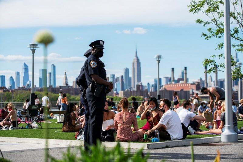 圖為紐約民眾到公園透氣,一旁有戴口罩的警員在旁留意群眾的社交距離。(路透)