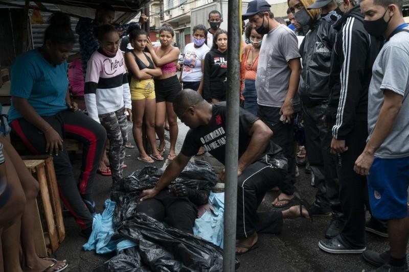 阿萊茂住宅區居民圍觀死者遺體。(美聯社)
