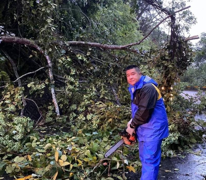 日月潭環湖公路因雨造成路樹倒塌,日月村長黃益琪手持電鋸協助進行清理工作。(記者謝介裕翻攝)