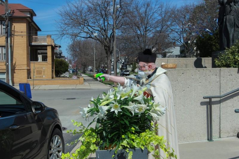 美國底特律一名律師,在疫情期間改以水槍向教徒灑聖水。(美聯社)