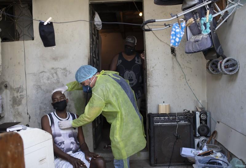 武漢肺炎(新型冠狀病毒病,COVID-19)疫情猖獗,肆虐拉丁美洲,秘魯與智利的首都病床佔用率分別高達80%與90%,醫療系統嚴重緊繃。而巴西在過去24小時內,新增1179例死亡病例,突破單日死亡人數新高。圖為巴西醫師Willie Baracho前往里約熱內盧(Janeiro)的貧民窟,為疑似病例進行檢疫。(美聯社)