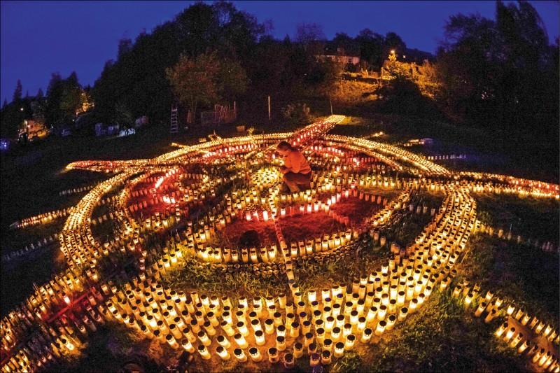 一名德國婦女19日在圖林根州市鎮采拉—梅利斯,點亮排列成十字架形狀的蠟燭,紀念8千多疫情受難者。(法新社)