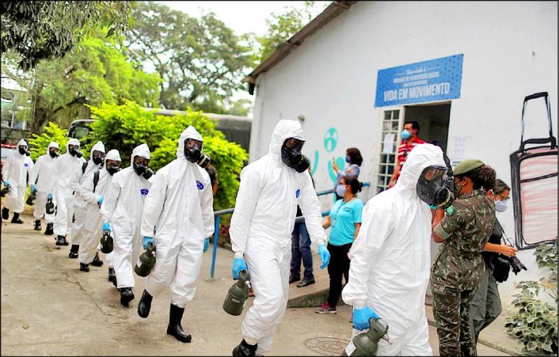 身穿全套防護裝備的巴西陸軍官兵,十四日在巴西第二大城里約熱內盧政府管理的安養中心消毒。巴西的武漢肺炎疫情急遽惡化,十九日單日死亡人數首度破千。(路透)