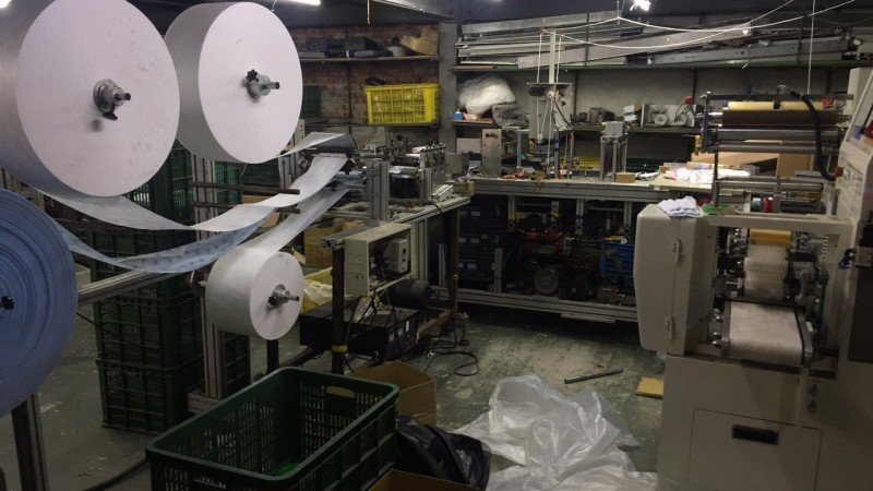 檢警調人員當場查扣高達38萬餘片口罩,部分外包裝標示為醫療口罩,另扣得醫療口罩靜電濾材111箱、每箱4000公尺等證物。(記者鄭淑婷翻攝)