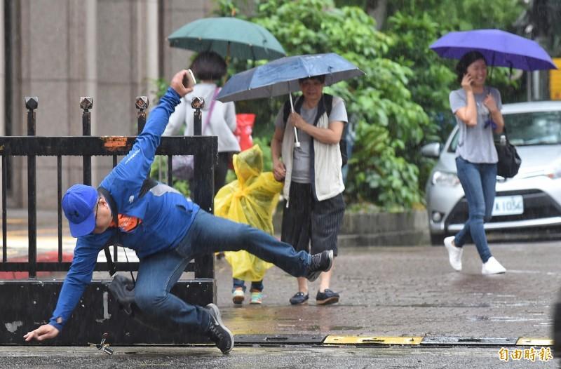 氣象局提醒,豪雨、大雨來襲時,民眾應注意強陣風,外出步行應留意自身安全。(資料照)