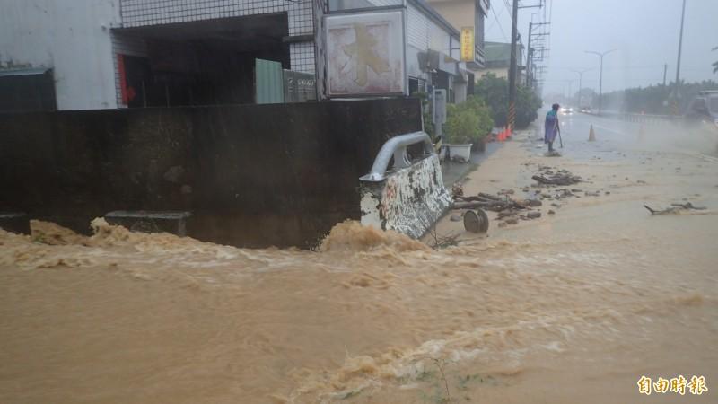 大水沖至旗南二路公路上。(記者許麗娟攝)
