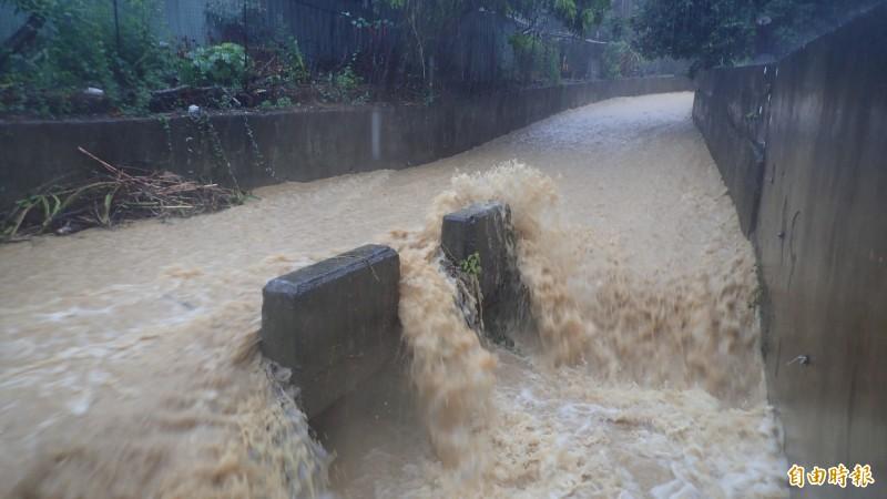 大水將土石、樹枝沿著排水溝沖下來,一旁的產業道路也成了小河。(記者許麗娟攝)