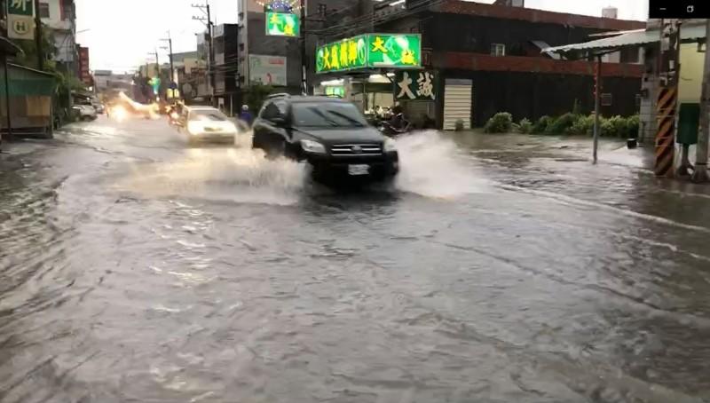 岡山區嘉興路一帶淹水,車輛經過水花四濺。(翻攝畫面)