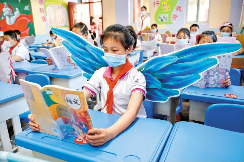 中國山西省省會太原市一所小學的學生,上課時戴著「翅膀」保持社交距離,避免感染武漢肺炎。(法新社)