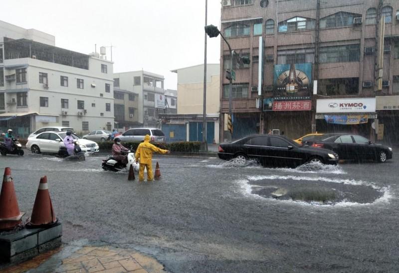 楠梓區道路人孔蓋冒水,員警到場指揮交通。(記者蔡清華翻攝)