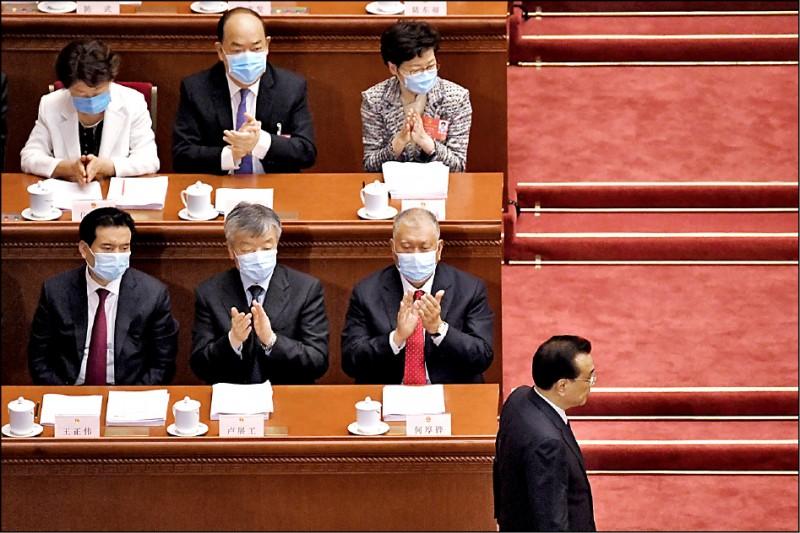 香港特首林鄭月娥(圖上排左三)廿二日在北京列席甫開幕的第十三屆中國全國人民代表大會第三次會議。她在中國國務院總理李克強結束發言回座時鼓掌。 (法新社)