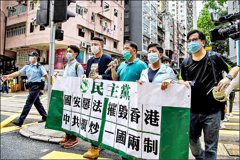 香港民主黨人士廿二日持標語遊街抗議中國人大擬制定香港版國安法。(法新社)