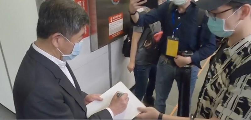 中央流行疫情指揮中心指揮官陳時中搭乘高鐵時,有民眾請他簽名。(指揮中心提供)
