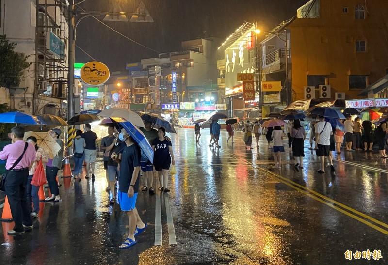 墾丁晚間下起大雨 民眾撐傘等待爭睹阿中部長