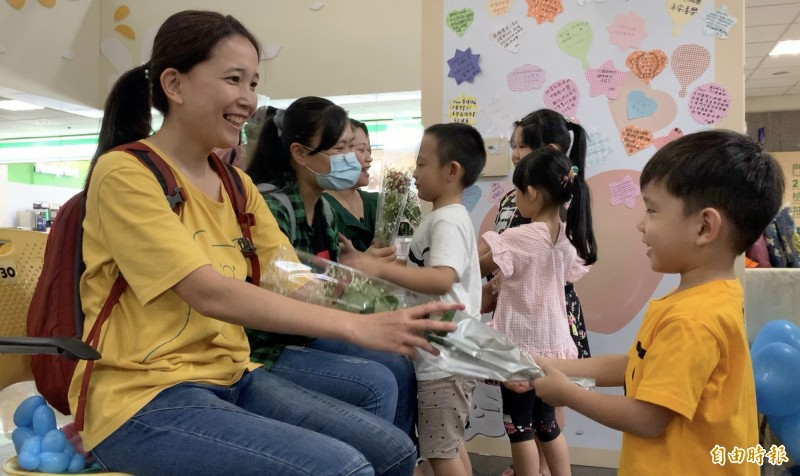 防疫護理師媽媽們開心接受孩子的獻花感謝。(記者蔡淑媛攝)